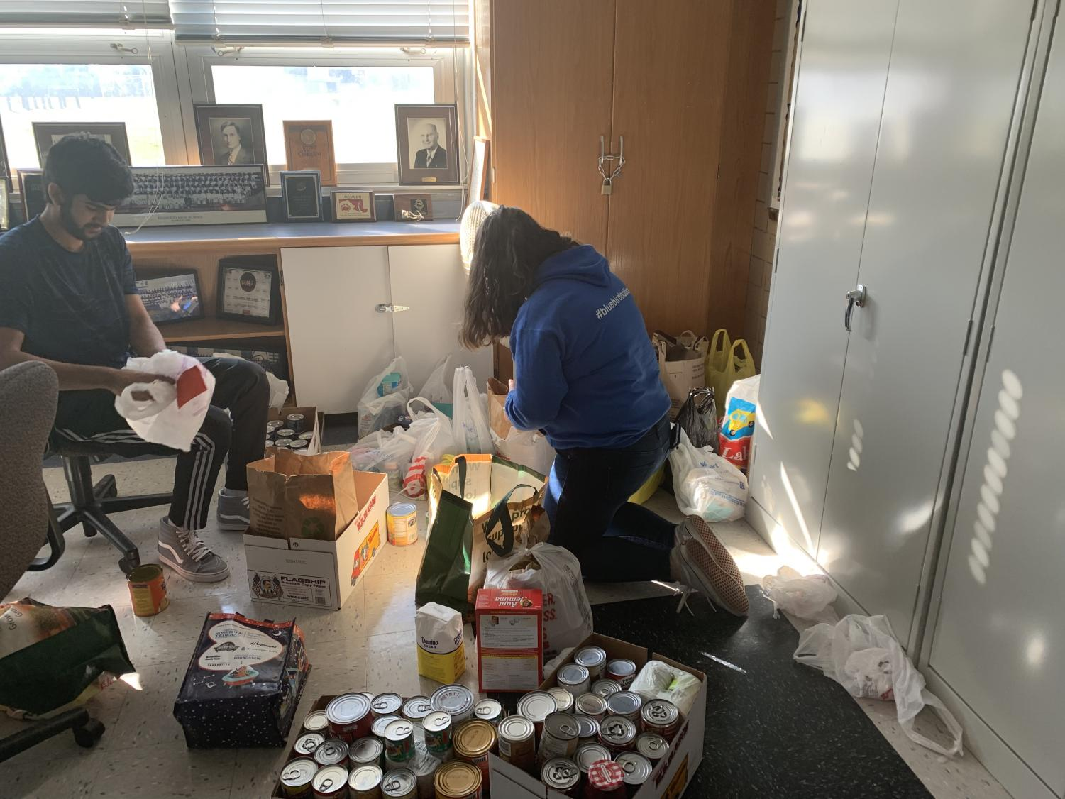 NHS President Shawaiz Abbasi and Vice President Caroline Harris sort and organize all the food donated during the Thanksgiving holiday food drive.
