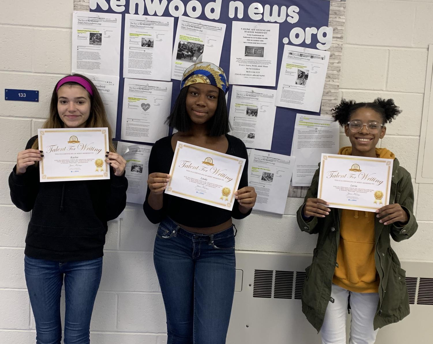 Three journalism students showcasing their announcement for their upcoming short story in a book anthology.